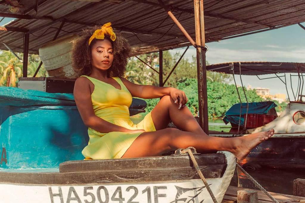 foto de quince a mujer luciendo estilo afro en el pelo con vestido amarillo sentado sobre un viejo bote anclado en el puerto en un dia soleado