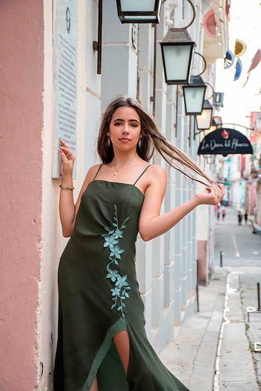 quinceañera cubana en vestido verde sosteniendo su cabello rubio en la habana