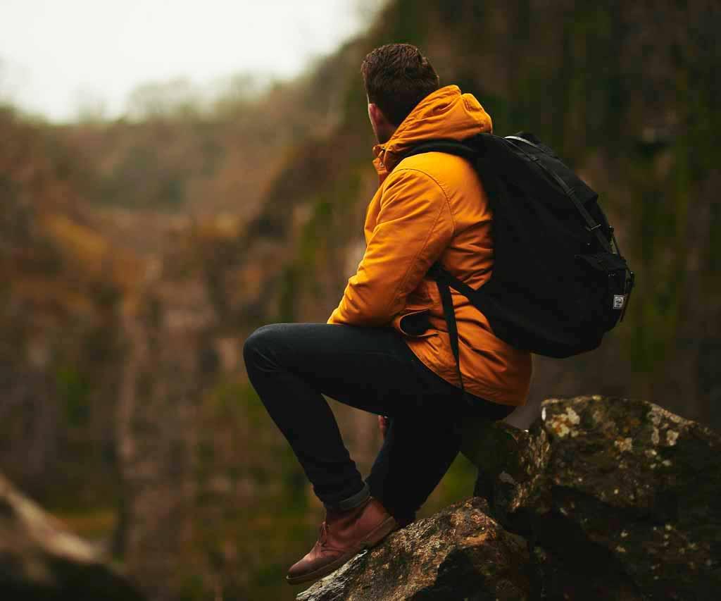 hombre sentado sobre roca con chaqueta naranja y mochila negra duranta una excursion en cuba