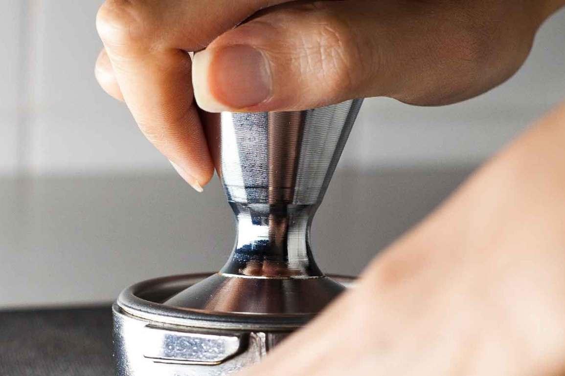 Mano sobre tamper de café