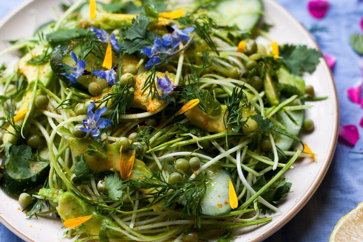 plato de fideos de calabacín con aguacate, pepino, cilantro, flores lobelias, guisantes y pétalos de crisantemo