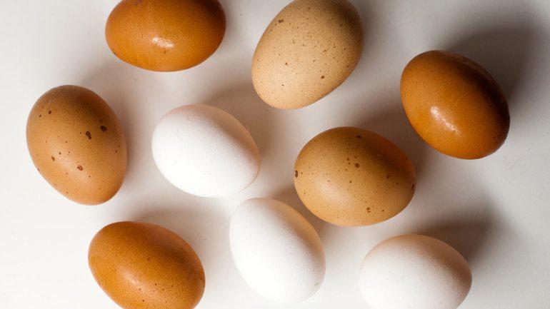 Huevos blancos y marrones sobre mesa blanca