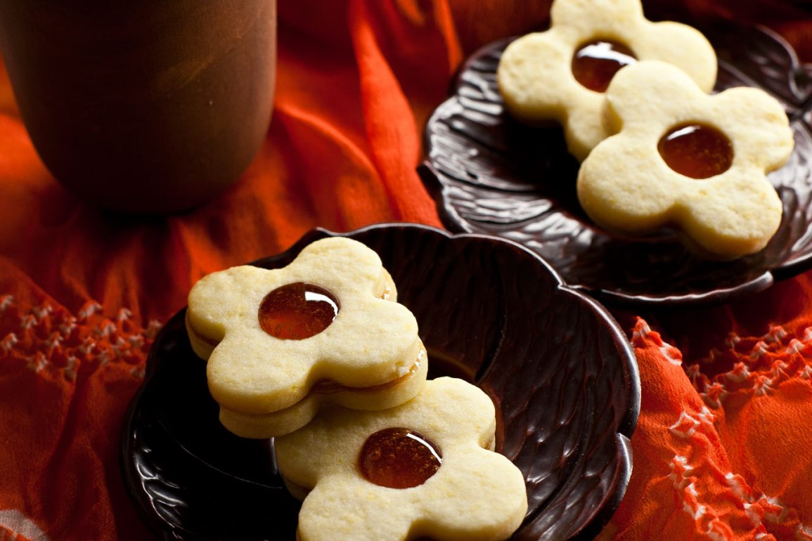Galletas de masa sablée rellenas con jalea de membrillo sobre platos individuales