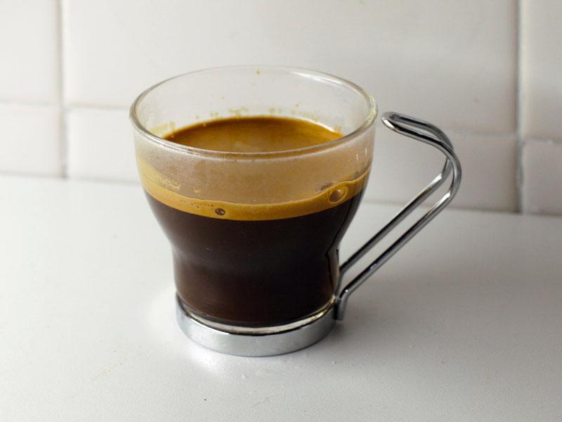 Café espresso en taza de vidrio y asa de metal sobre una mesa