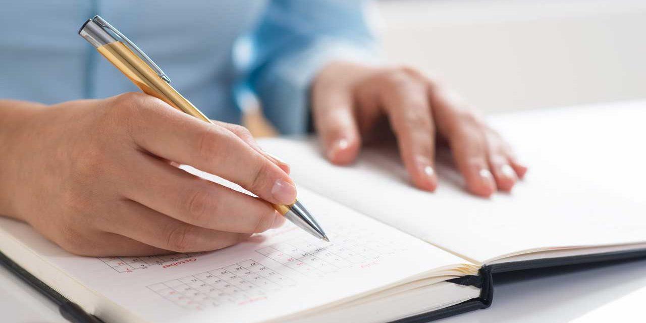 Persona tomando notas en su agenda