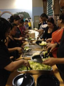 Volunteers plate each meal and serve them to the families at their table