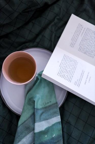 mouchoir en tissu bio à côté d'un livre et une tasse de café