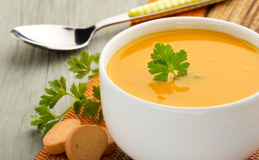25835479 - bowl of soup, parsley and croutons on wooden table