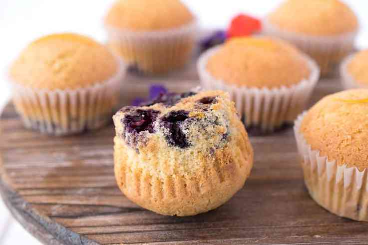 A muffin turned upside down showing the blueberries on the bottom