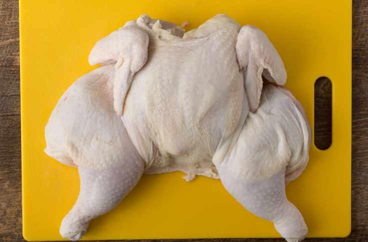 A butterflied chicken on a yellow cutting board