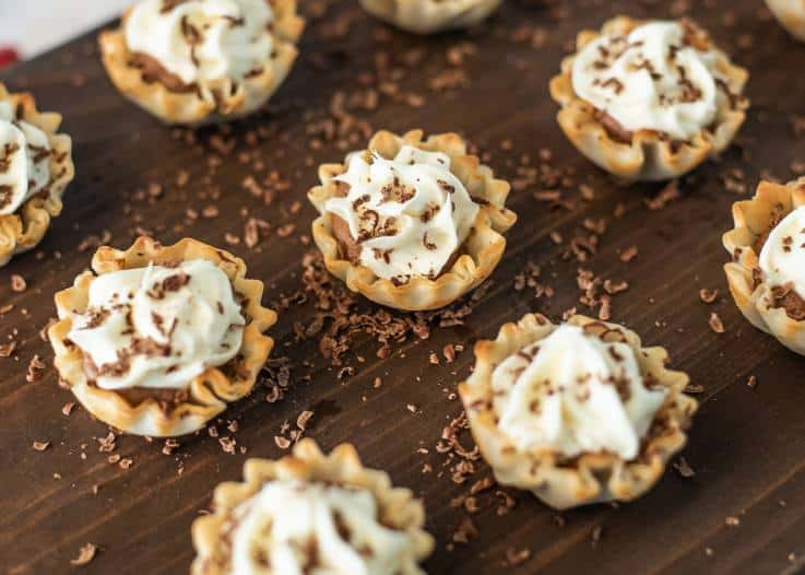 A selection of Chocolate Mousse Cream Cheese Phyllo Dessert Cups on a serving board with shaved chocolate
