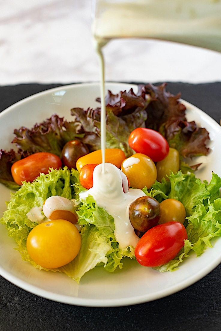 Chunky blue cheese dressing being poured over lettuce and cherry tomatoes