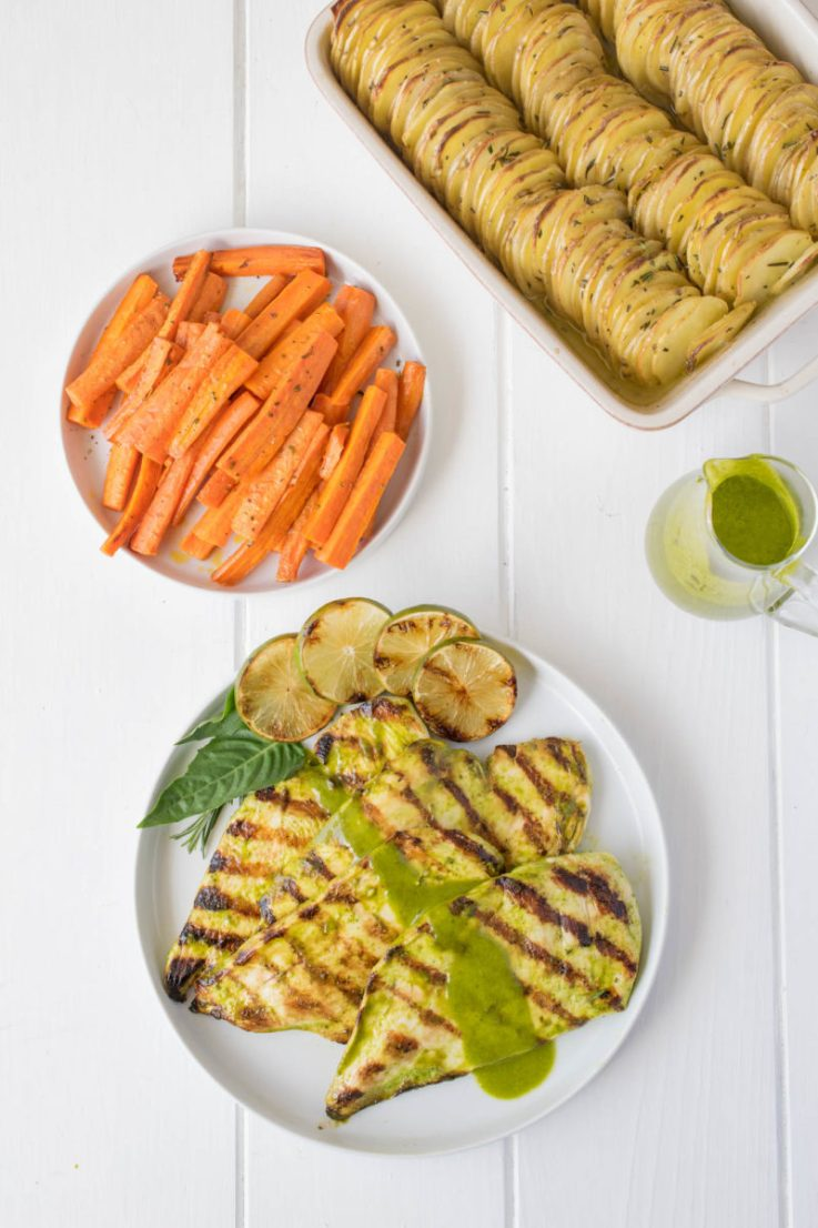 A plate of grilled chicken, cooked carrots and crispy layered rosemary potatoes ready to be served