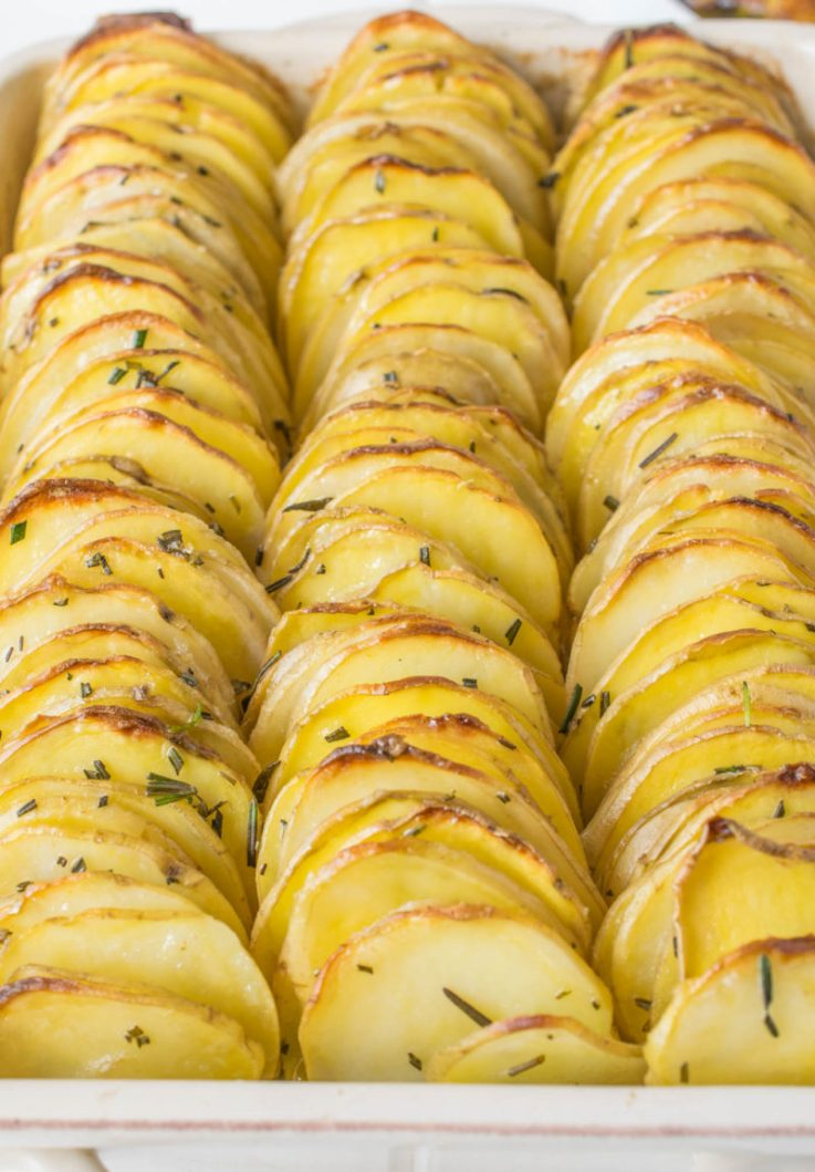 A closeup of crispy layered rosemary potatoes in a casserole dish, brown and crispy
