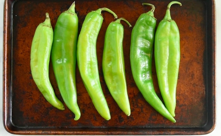 Green hatch chiles are lined up on a baking sheet ready to be broiled