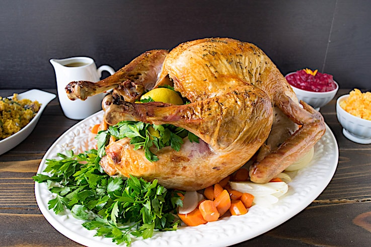 A roast turkey on a white plate garnished with fresh parsley, lemon and carrots