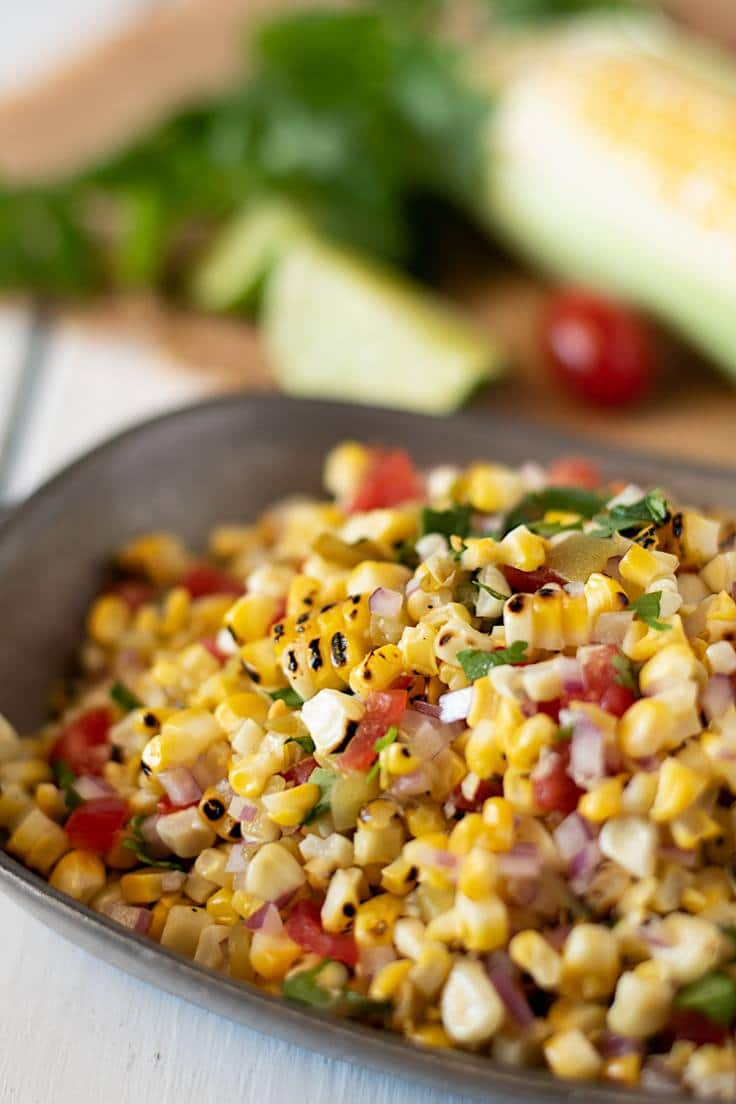 A closeup showing the grilled corn kernels and colorful ingredients in a grey bowl