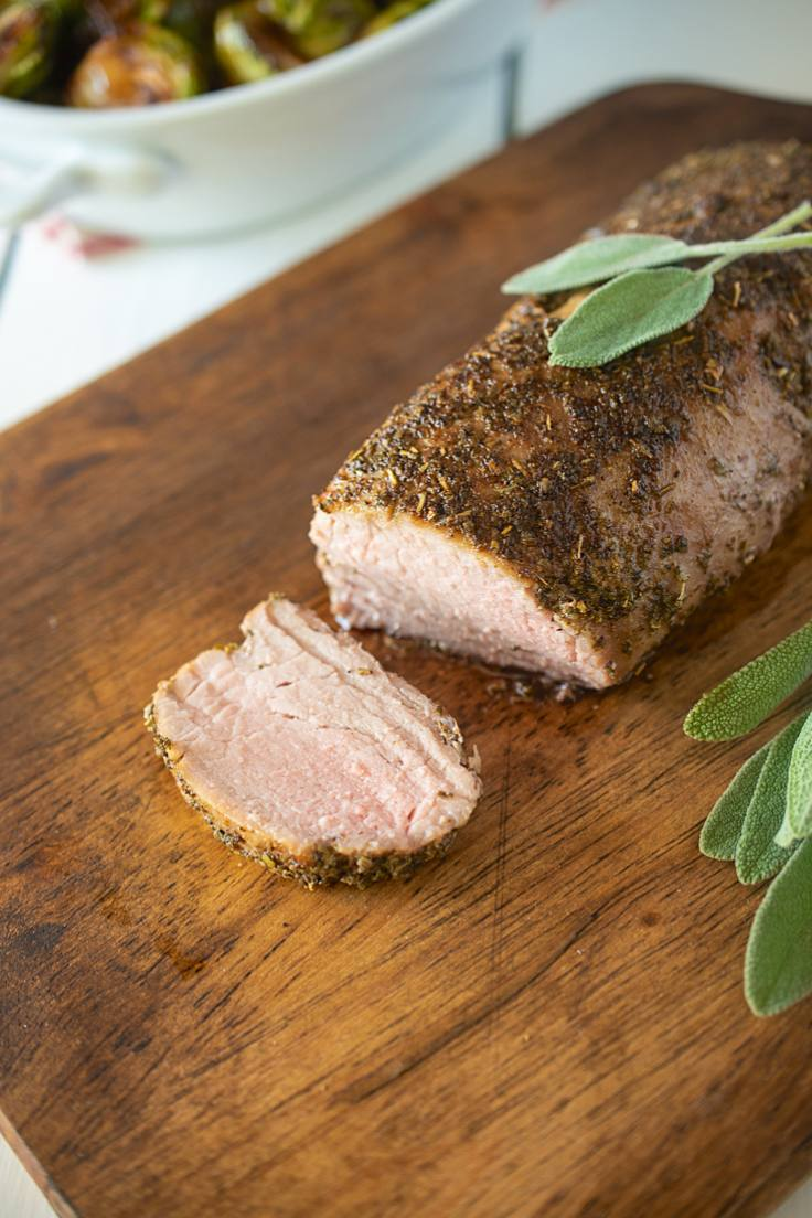 Sage rubbed pork tenderloin on a serving board sliced