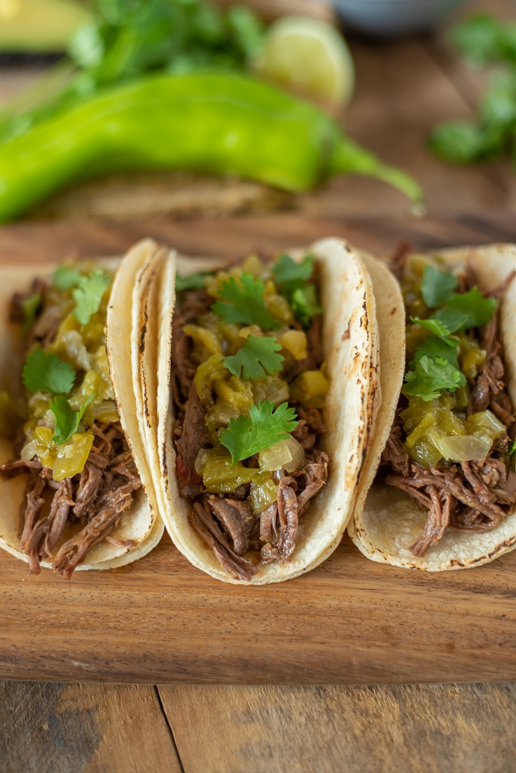 3 Sonoran shredded beef tacos on a board with hatch chile sauce and cilantro