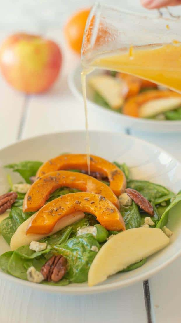 Orange vinaigrette being drizzled onto the salad