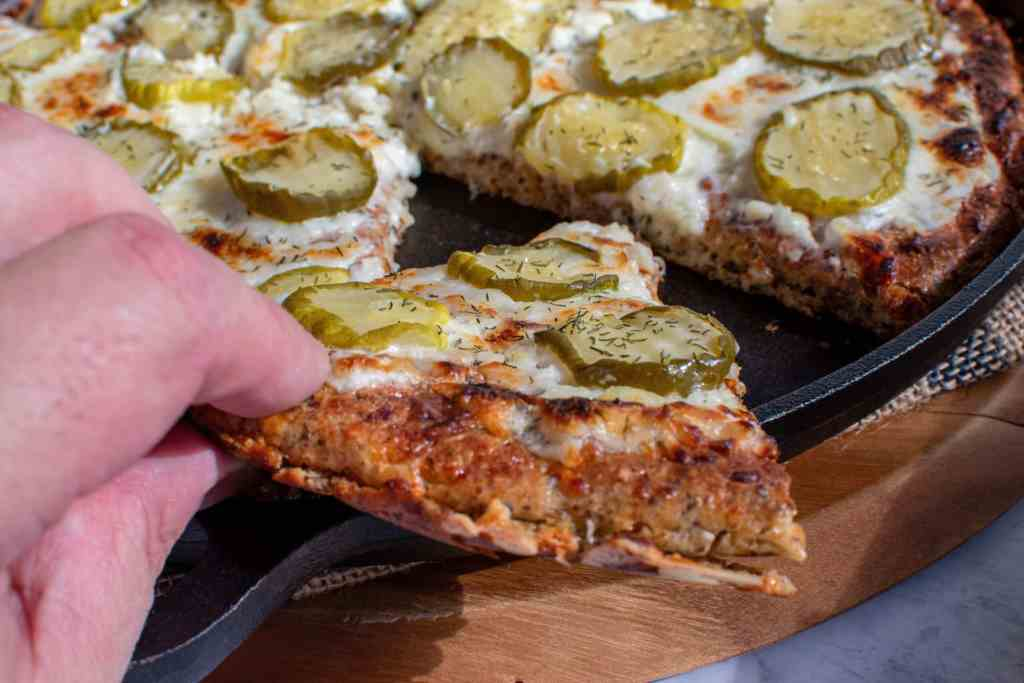 grabbing a slice of low carb dill pickle pizza from cast iron skillet