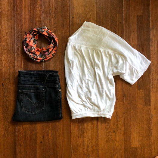 A pair of jeans, a shirt, and a scarf are laid out on the floor for display.