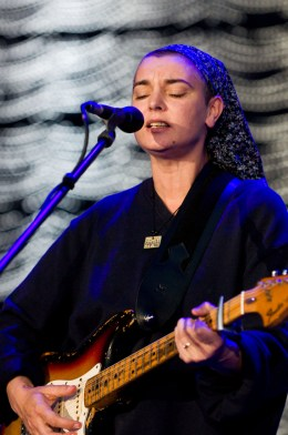 A picture of Sinéad O'Connor performing on stage.