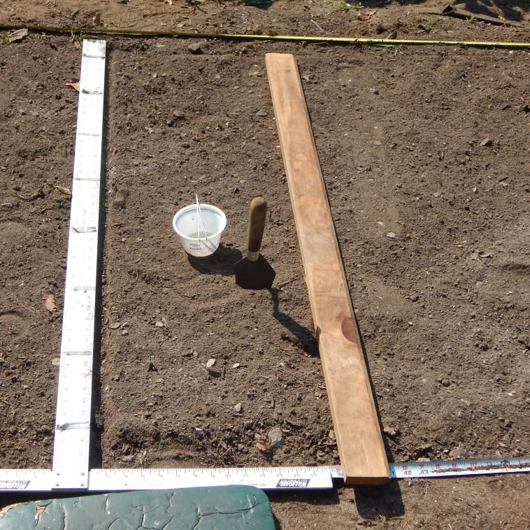 HERE IS MY CARROT PLANTING RIG:  A TAPE MEASURE EXTENDED THE LENGTH OF THE BED, MY TRUSTY SHEETROCK SQUARE, MY PLANTING BOARD USED TO MAKE THE PLANTING FURROW, A CONTAINER TO HOLD THE SEEDS AND A PAIR OF TWEEZERS TO  HANDLE THE SEEDS