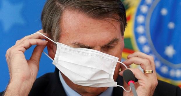 Presidente Bolsonaro tenta colocar uma máscara e acaba se atrapalhando e cobre os olhos