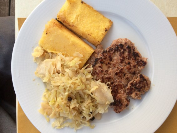 Polenta with cabbage and local meat sausage.