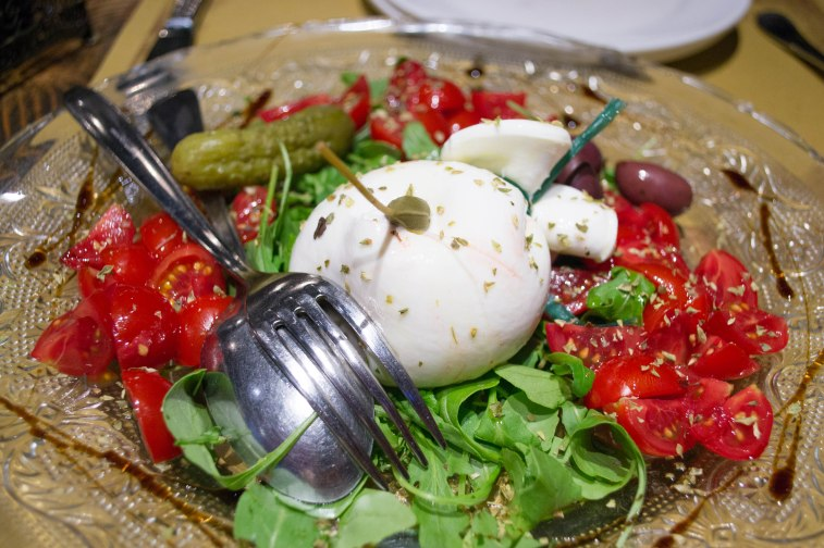 Caprese salad with spinach, basil, tomatoes, a pickle, and delicious burrata cheese with a caper inside.
