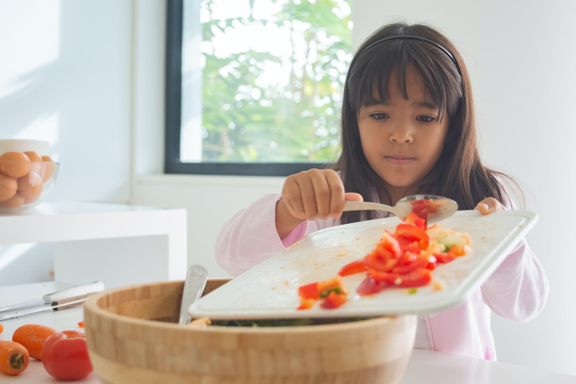 girl holding chopping board with sliced tomatoes
