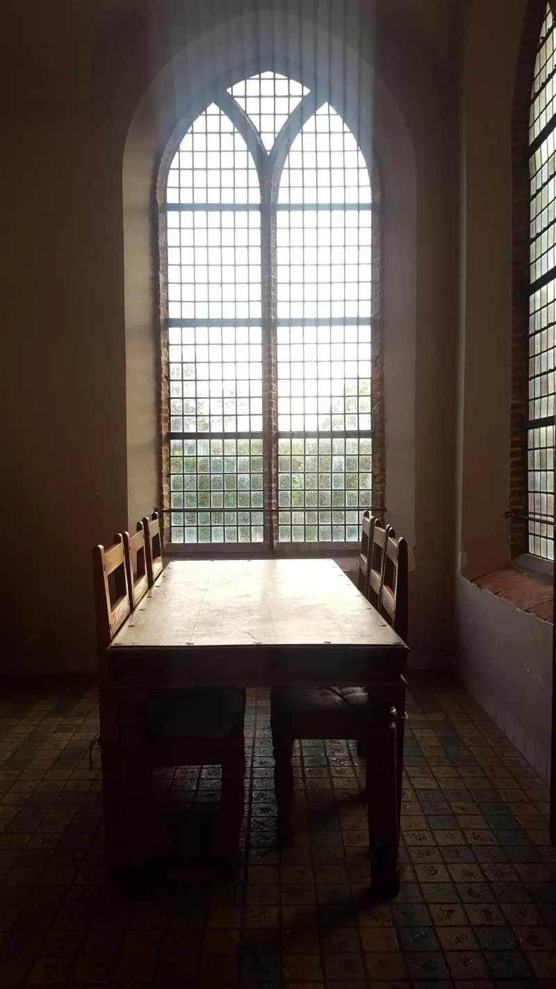 Wooden table with mullioned windows in a Netherlands Castle Hotel