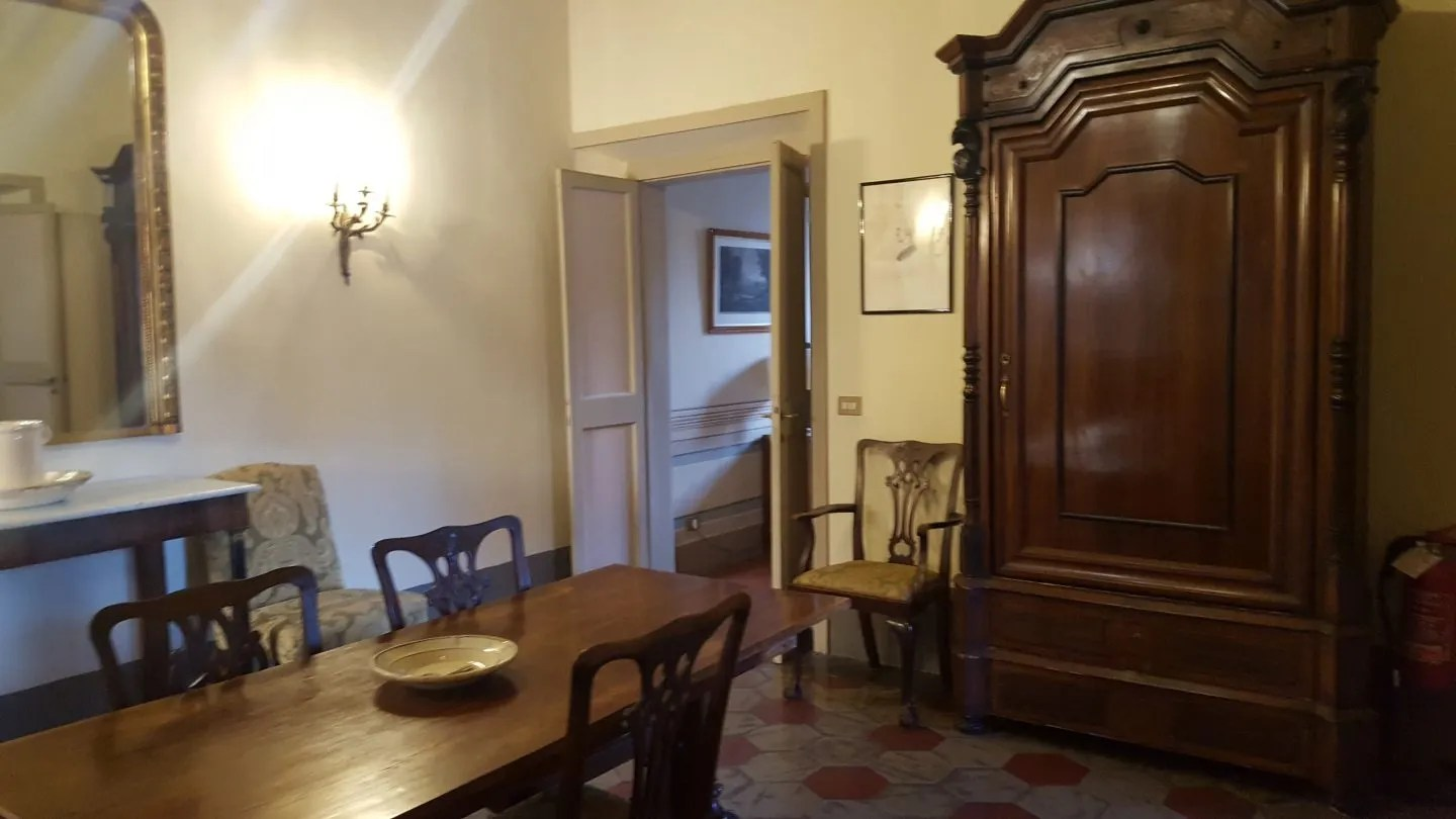 Interior Landmark Trust Rome rental. Dark wood dining table and chairs, large dark wood wooden wardrobe, ceramic tiled floor