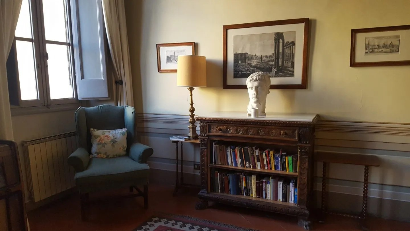 Living room interior Landmark Trust Rome with blue wing chair by window, bookshelf with a classical roman bust on top.