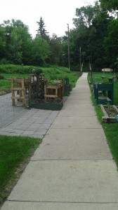 The Preston Street Apartments Community Garden, as viewed from outside the building. The in-ground portion of the garden is past the tables to the left. This photo was taken after the first phase of the garden improvement project was completed. The paving stone and all the tables to the left of the sidewalk are new additions.