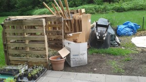 """All of the building supplies, tools, and other garden miscellanea are carefully piled in one end of the garden, next to the compost bins. This is an attempt to minimize the perceived messiness of the garden and avoid accusations of looking """"hillbilly."""""""