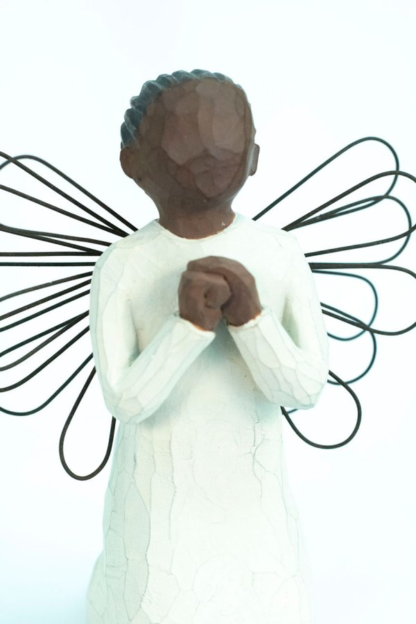 angel figurine with wire wings, praying hands, closeup