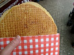 Trying a stroopwafel on the streets of Amsterdam