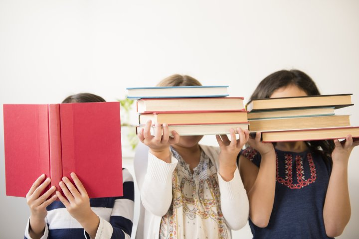 Girls holding books in front of faces