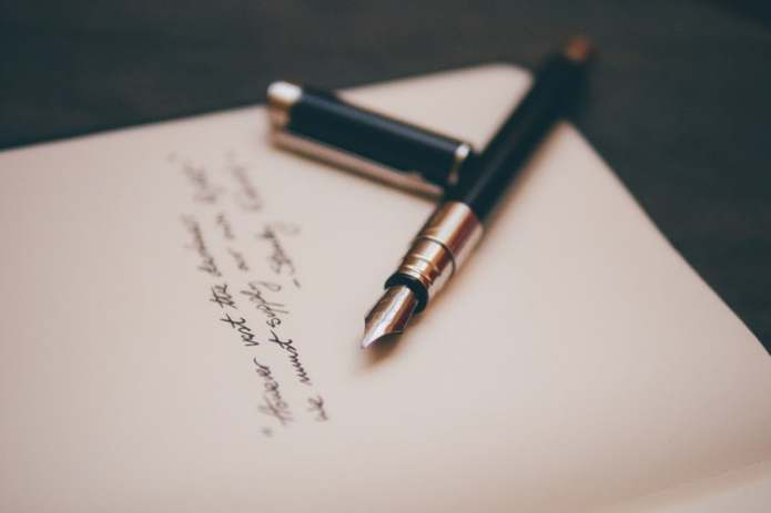Fountain pen on writing stationery photo