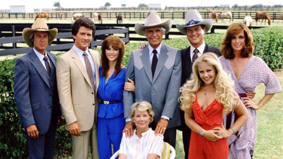 A promotional still from the American television series 'Dallas' shows the cast assembled on the property of the Southfork ranch, on the outskirts of Dallas, Texas, 1979. From left, American actors Steve Kanaly (as Ray Krebbs), Patrick Duffy (as Bobby Ewing), Victoria Principal (as Pamels Barnes Ewing), (sitting), Barbara Bel Geddes (as Eleanor Southworth 'Miss Ellie' Ewing), Jim Davis (1909 - 1981) (as John Ross 'Jock' Ewing), Larry Hagman (as John Ross 'J.R.' Ewing, Jr.), Charlene Tilton (as Lucy Ewing) (in red), and Linda Gray (as Sue Ellen Ewing). (Photo by CBS Photo Archive/Getty Images) decade