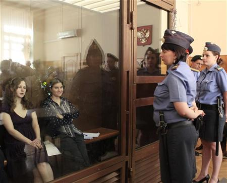"Members of the female punk band ""Pussy Riot"" sit in the defendant's cell before a court hearing in Moscow"