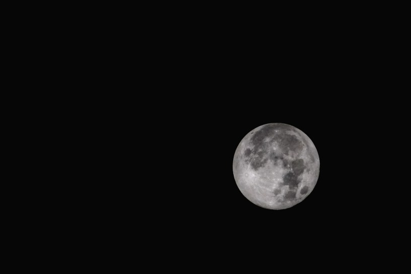 Grayscale photo of the moon, with a black sky in the background
