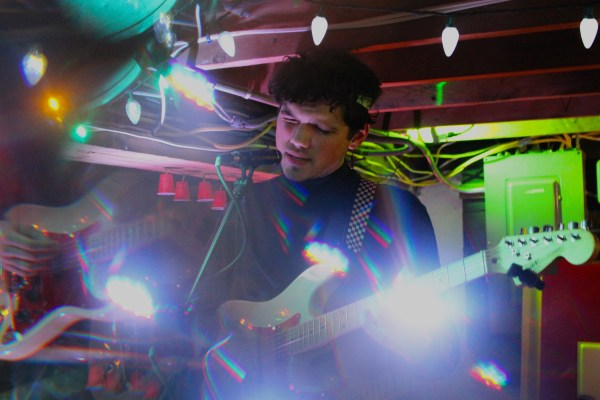 a musician plays an electric guitar with a colorful light show