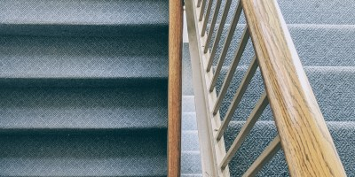 Photograph of overlapping staircases and bannisters with blue carpet