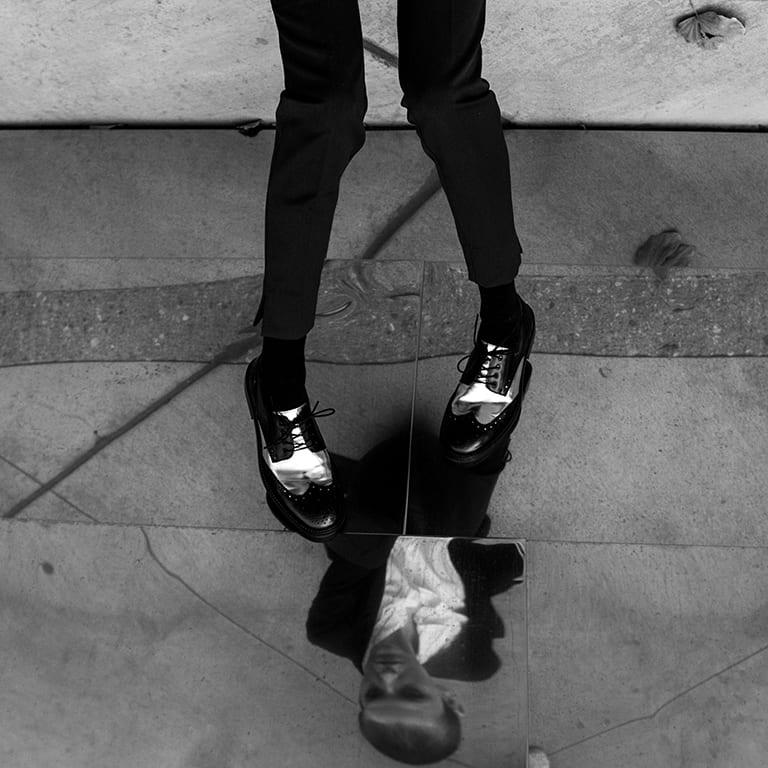 person looking at self image in reflection on floor. Nik Kacy Shoes. Photo Credit: Ana Karotkaya