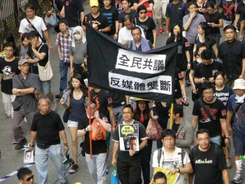 Group of people from Hong Kong marching with signs