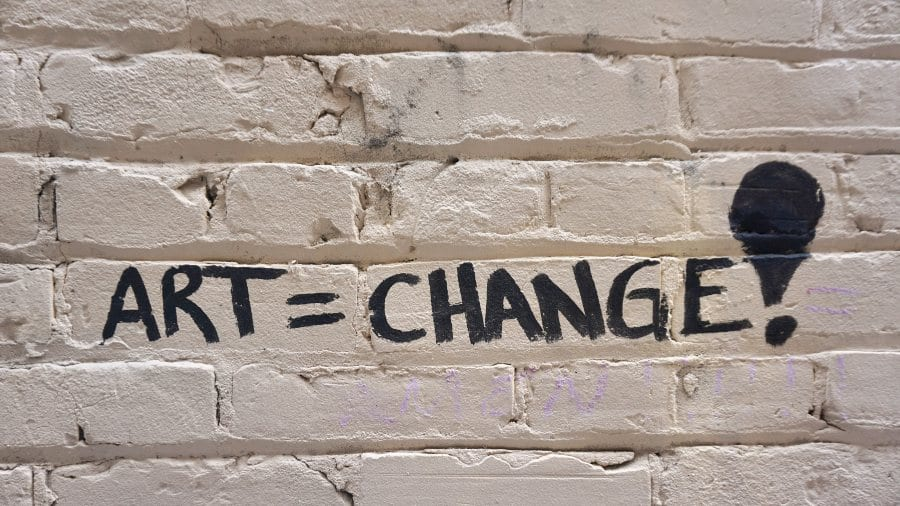 Photography showing graffiti that says Art = Change!