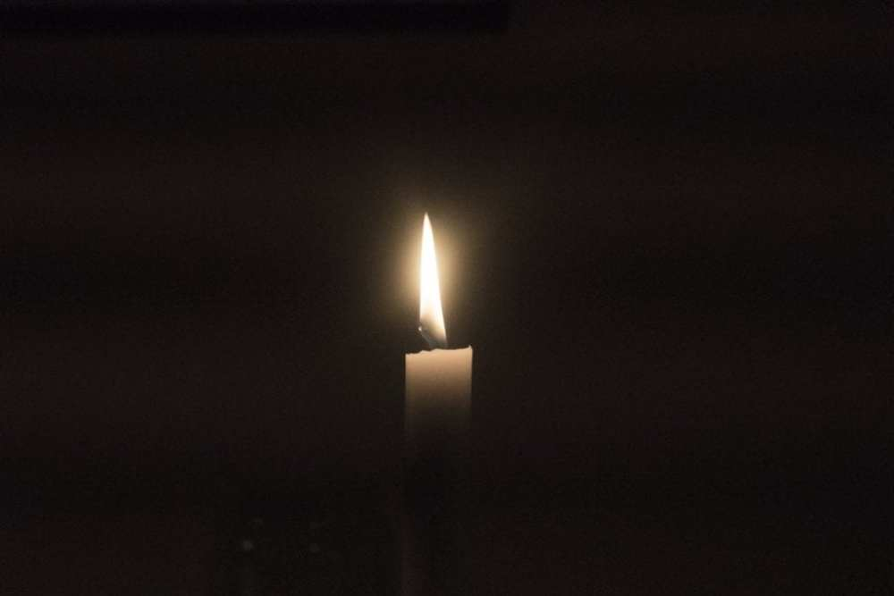 A small, white, lit candle lights up a dark background